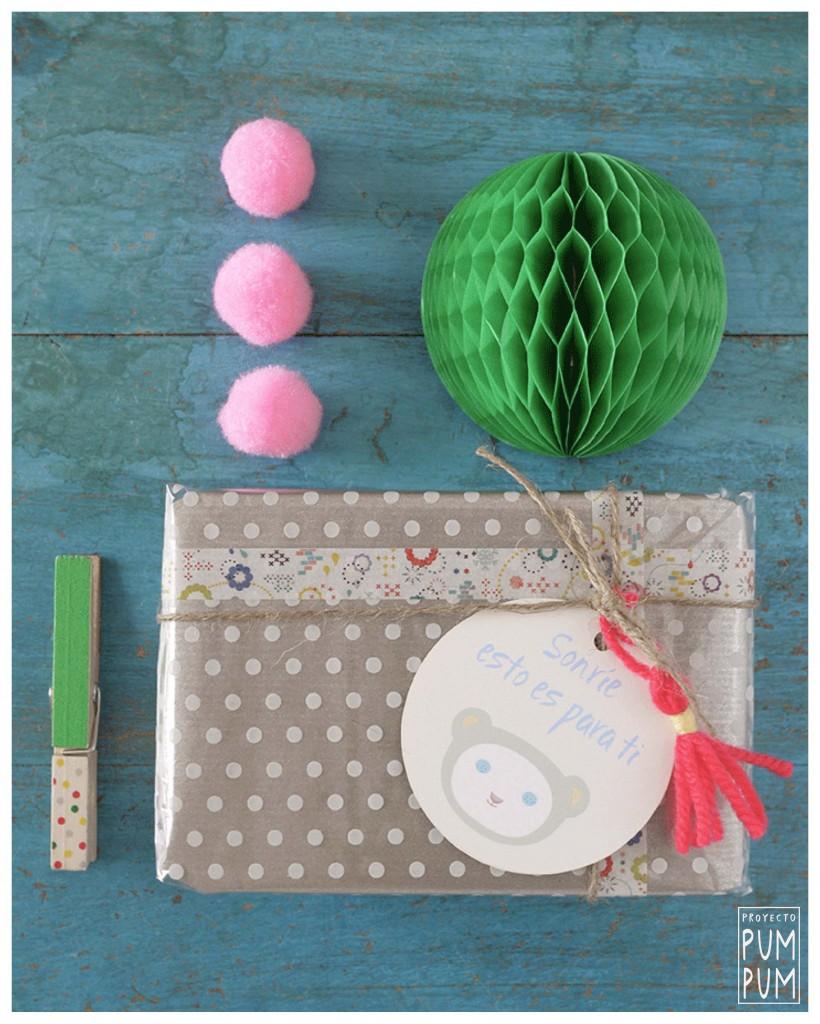 Materiales: etiquetas Pum Pum, washi tape, cuerda, pompón de lana papel de plástico de topos y papel craft.